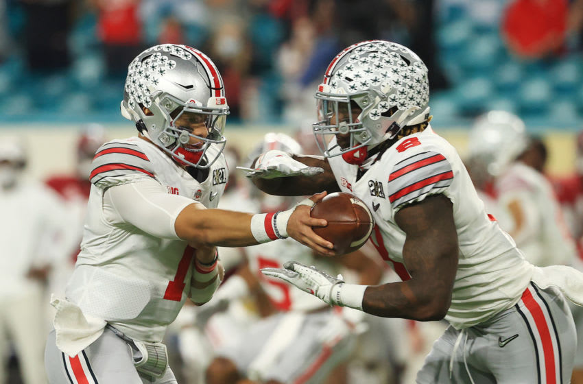 MIAMI GARDENS, FLORIDA - JANUARY 11: Justin Fields #1 of the Ohio State Buckeyes hands off to Trey Sermon #8 during the first quarter of the College Football Playoff National Championship game against the Alabama Crimson Tideat Hard Rock Stadium on January 11, 2021 in Miami Gardens, Florida. (Photo by Mike Ehrmann/Getty Images)
