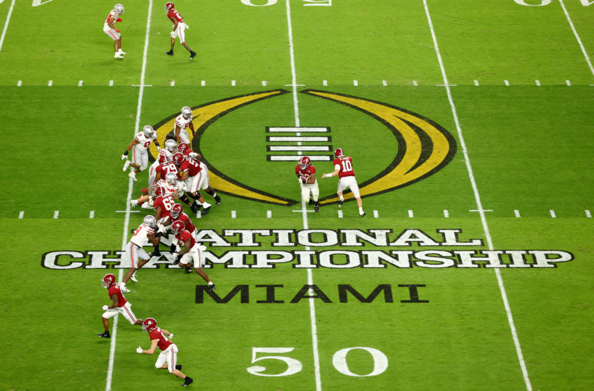 MIAMI GARDENS, FL - JANUARY 11: Mac Jones #10 of the Alabama Crimson Tide hands off to Najee Harris #22 against the Ohio State Buckeyes during the College Football Playoff National Championship held at Hard Rock Stadium on January 11, 2021 in Miami Gardens, Florida. (Photo by Jamie Schwaberow/Getty Images)