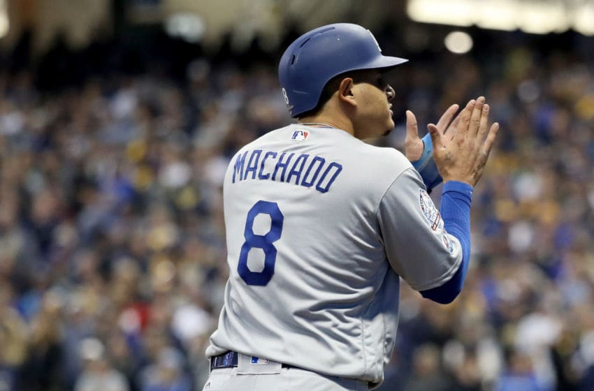 MILWAUKEE, WI - OCTOBER 12: Manny Machado #8 of the Los Angeles Dodgers celebrates after hitting an RBI single to score Chris Taylor #3 and Joc Pederson #31 against the Milwaukee Brewers during the eighth inning in Game One of the National League Championship Series at Miller Park on October 12, 2018 in Milwaukee, Wisconsin. (Photo by Rob Carr/Getty Images)