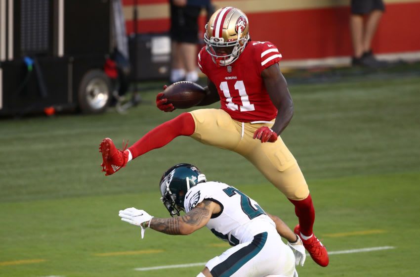 SANTA CLARA, CALIFORNIA - OCTOBER 04: Brandon Aiyuk #11 of the San Francisco 49ers leaps over Marcus Epps #22 of the Philadelphia Eagles to score a touchdown against the Philadelphia Eagles during the first quarter at Levi's Stadium on October 04, 2020 in Santa Clara, California. (Photo by Ezra Shaw/Getty Images)