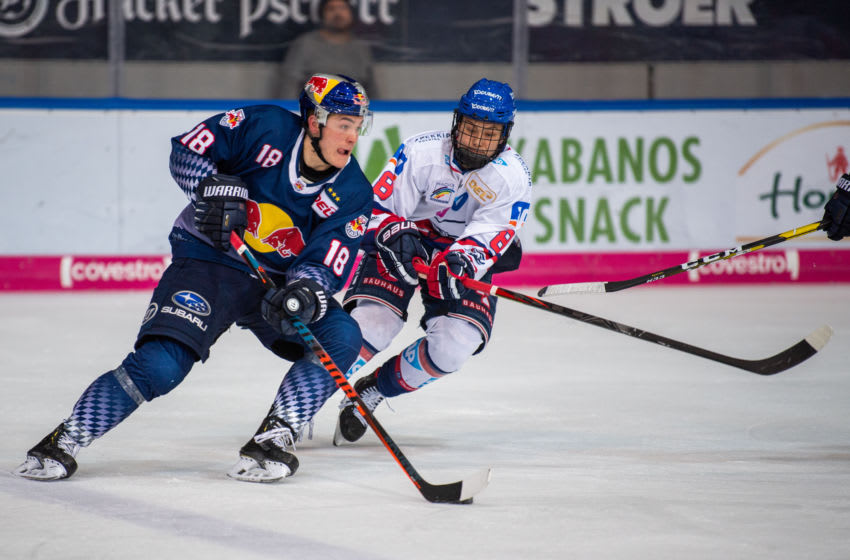 08 December 2019, Bavaria, Munich: Ice hockey: DEL, EHC Red Bull Munich - Adler Mannheim, main round, 25th matchday in the Olympic Ice Stadium Munich. Justin Schütz (l) from Red Bull Munich plays against Tim Stützle from Adler Mannheim at the Puck. Photo: Lino Mirgeler/dpa (Photo by Lino Mirgeler/picture alliance via Getty Images)