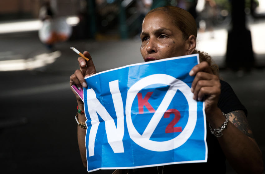 NEW YORK, NY - JULY 14: A neighborhood resident holds up a 'No K2' sign, July 14, 2016 on the border of the Bedford-Stuyvesant and Bushwick neighborhoods in the Brooklyn borough of New York City. Following a wave of suspected K2 overdoes on Tuesday, New York City police raided five convenience stores on Wednesday. (Photo by Drew Angerer/Getty Images)
