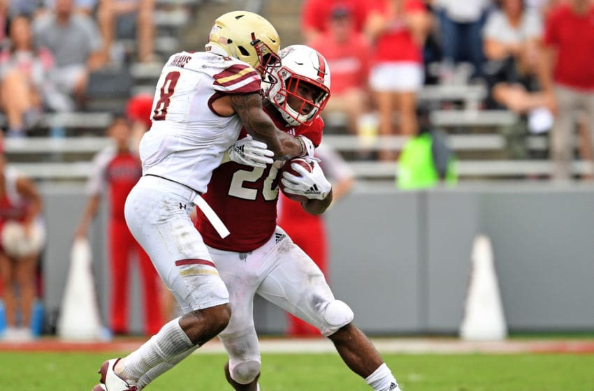 RALEIGH, NC - OCTOBER 06: Will Harris #8 of the Boston College Eagles tackles Ricky Person Jr. #20 of the North Carolina State Wolfpack during their game at Carter-Finley Stadium on October 6, 2018 in Raleigh, North Carolina. North Carolina State won 28-23. (Photo by Grant Halverson/Getty Images)