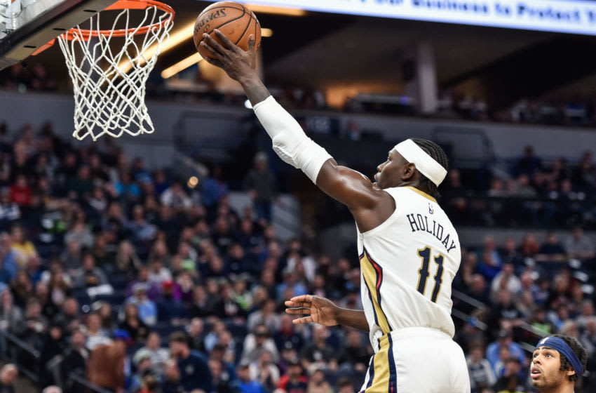 Mar 8, 2020; Minneapolis, Minnesota, USA; New Orleans Pelicans guard Jrue Holiday (11) goes to the basket as Minnesota Timberwolves guard D'Angelo Russell (0) looks on during the second quarter at Target Center. Mandatory Credit: Jeffrey Becker-USA TODAY Sports