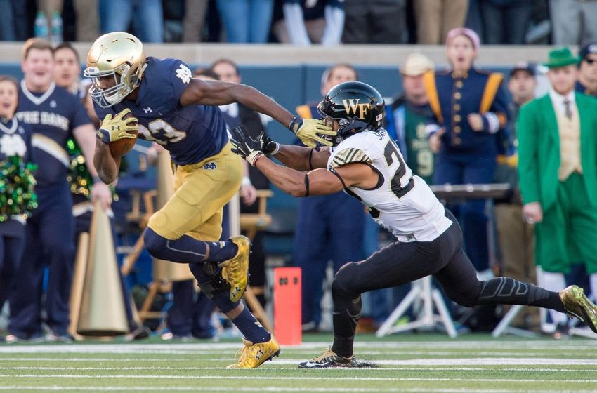 Nov 14, 2015; South Bend, IN, USA; Notre Dame Fighting Irish running back Josh Adams (33) breaks free of Wake Forest Demon Deacons safety Ryan Janvion (22) for a 98 yard touchdown run in the second quarter at Notre Dame Stadium. Mandatory Credit: Matt Cashore-USA TODAY Sports