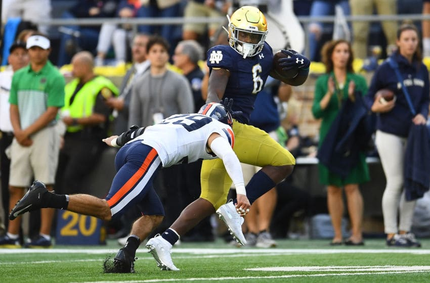 SOUTH BEND, INDIANA - SEPTEMBER 28: Tony Jones Jr. #6 of the Notre Dame Fighting Irish avoids a tackle by Joey Blount #29 of the Virginia Cavaliers during the second half at Notre Dame Stadium on September 28, 2019 in South Bend, Indiana. (Photo by Stacy Revere/Getty Images)