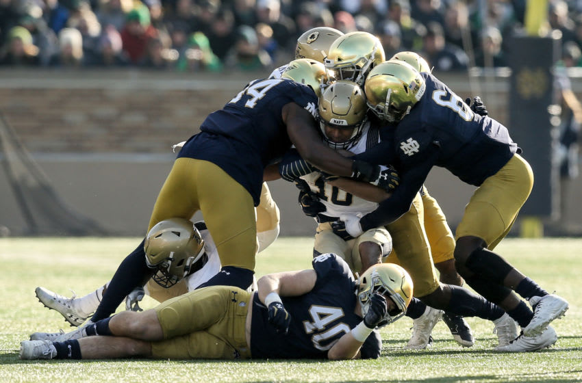 SOUTH BEND, INDIANA - NOVEMBER 16: Malcolm Perry #10 of the Navy Midshipmen is tackled by Jamir Jones #44 and Jeremiah Owusu-Koramoah #6 of the Notre Dame Fighting Irish in the first quarter at Notre Dame Stadium on November 16, 2019 in South Bend, Indiana. (Photo by Dylan Buell/Getty Images)