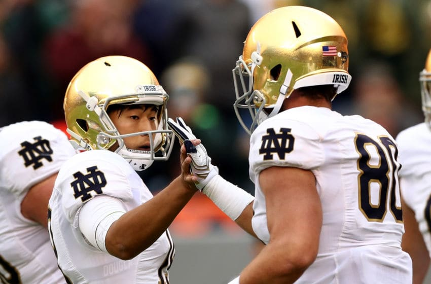 EAST RUTHERFORD, NJ - OCTOBER 01: Justin Yoon #19 of the Notre Dame Fighting Irish is congratulated by teammate Durham Smythe #80 of the Notre Dame Fighting Irish after Yoon made the extra point in the second half against the Syracuse Orange at MetLife Stadium on October 1, 2016 in East Rutherford, New Jersey.The Notre Dame Fighting Irish defeated the Syracuse Orange 50-33. (Photo by Elsa/Getty Images)