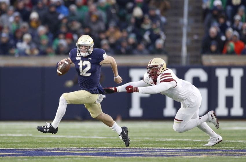 SOUTH BEND, IN - NOVEMBER 23: Ian Book #12 of the Notre Dame Fighting Irish avoids the pass rush from Richard Yeargin #2 of the Boston College Eagles in the second half at Notre Dame Stadium on November 23, 2019 in South Bend, Indiana. Notre Dame defeated Boston College 40-7. (Photo by Joe Robbins/Getty Images)