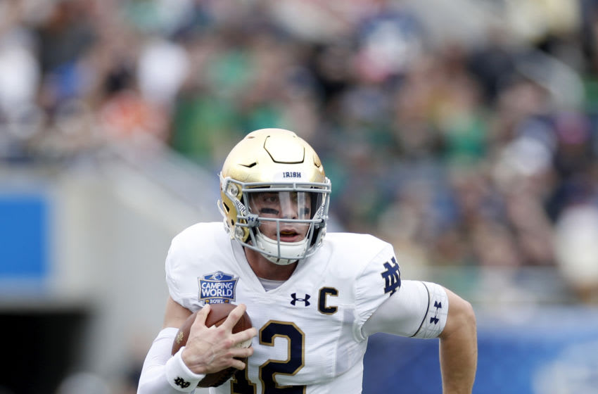 ORLANDO, FL - DECEMBER 28: Ian Book #12 of the Notre Dame Fighting Irish runs with the ball during the Camping World Bowl against the Iowa State Cyclones at Camping World Stadium on December 28, 2019 in Orlando, Florida. Notre Dame defeated Iowa State 33-9. (Photo by Joe Robbins/Getty Images)