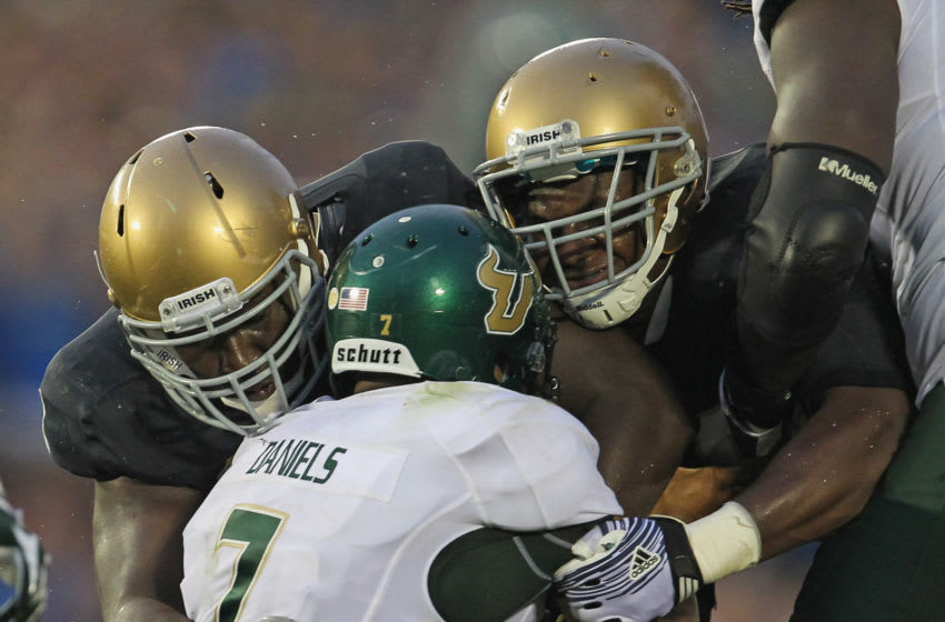 SOUTH BEND, IN - SEPTEMBER 03: Kapron Lewis-Moore #89 (L) and Darius Fleming #45 of the Notre Dame Fighting Irish bring down B.J. Daniels #7 of the University of South Florida Bulls at Notre Dame Stadium on September 3, 2011 in South Bend, Indiana. South Florida defeated Notre Dame 23-20.(Photo by Jonathan Daniel/Getty Images)