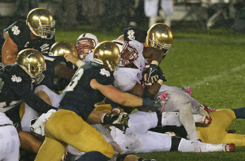 SOUTH BEND, IN - OCTOBER 13: Stepfan Taylor #33 of the Stanford Cardinal is stopped short of the goal by members of the Notre Dame Fighting Irish defense on the last play of the game at Notre Dame Stadium on October 13, 2012 in South Bend, Indiana. Notre Dame defeated Stanford 20-13 in overtime. (Photo by Jonathan Daniel/Getty Images)
