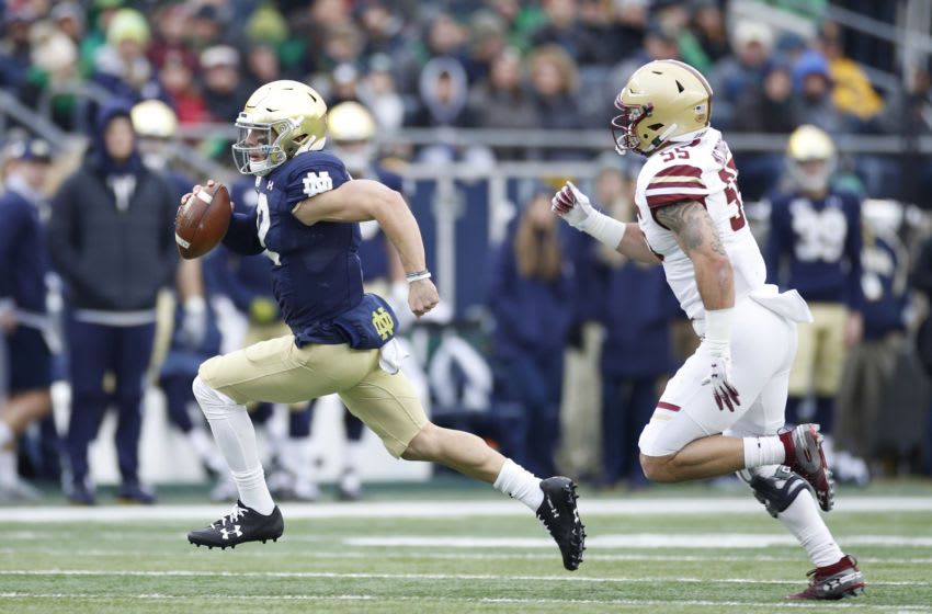 SOUTH BEND, IN - NOVEMBER 23: Ian Book #12 of the Notre Dame Fighting Irish runs with the ball against the Boston College Eagles in the first quarter at Notre Dame Stadium on November 23, 2019 in South Bend, Indiana. (Photo by Joe Robbins/Getty Images)