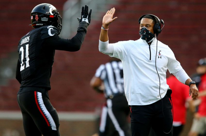 Cincinnati Bearcats defensive coordinator Marcus Freeman high fives Cincinnati Bearcats wide receiver Tyler Scott (21) as he comes off the field following a special teams play in the fourth quarter during an NCAA college football game against the Army Black Knights, Saturday, Sept. 26, 2020, at Nippert Stadium in Cincinnati. The Cincinnati Bearcats won 24-10. Army Black Knights At Cincinnati Bearcats Sept 26