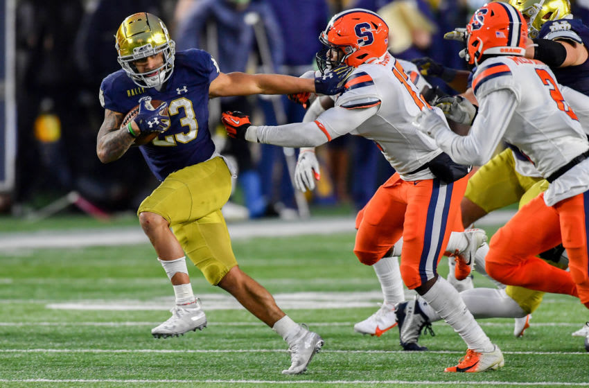 Dec 5, 2020; South Bend, Indiana, USA; Notre Dame Fighting Irish running back Kyren Williams (23) stiff arms Syracuse Orange linebacker Mikel Jones (13) in the third quarter at Notre Dame Stadium. Mandatory Credit: Matt Cashore-USA TODAY Sports