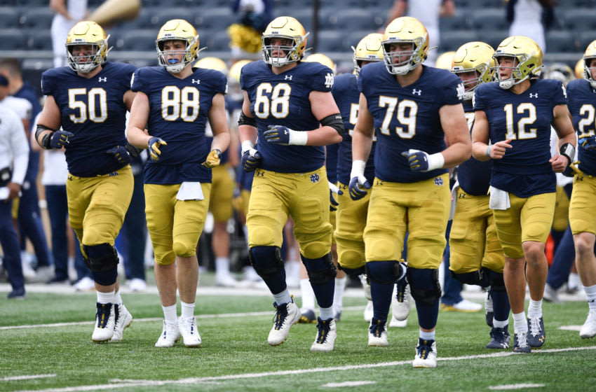 May 1, 2021; Notre Dame, Indiana, USA; Notre Dame Fighting Irish offensive lineman Rocco Spindler (50) tight end Mitchell Evans (88) offenisve lineman Michael Carmody (68) offensive lineman Tosh Baker (79) and quarterback Tyler Buchner (12) run onto the field in the second half of the Blue-Gold Game at Notre Dame Stadium. Mandatory Credit: Matt Cashore-USA TODAY Sports