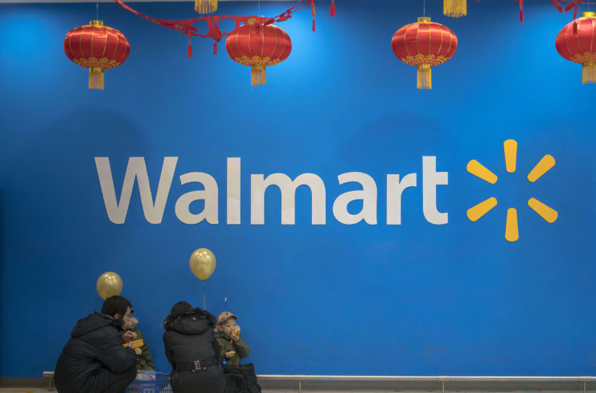 BEIJING, CHINA - 2017/01/15: A couple with their twin kids at the entrance of a Walmart store. To welcome Chinese traditional Spring Festival at the end of January, Walmart stores are decorated with Chinese lanterns and discount posters to attract customers. (Photo by Zhang Peng/LightRocket via Getty Images)