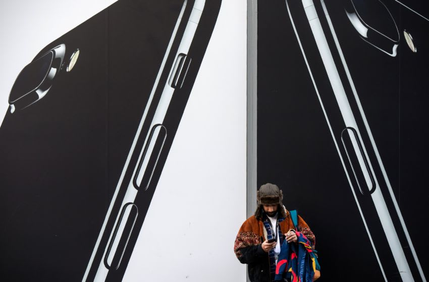 A man checks his phone next to billboards advertising the an Apple iPhone 7 smartphone as he stands on Oxford Street in London on March 7, 2017. Britain's Finance minister Philip Hammond earlier this week said he would keep chopping away at the deficit to get Britain fit to face Brexit, as he prepares to deliver his budget on March 8. / AFP PHOTO / CHRIS J RATCLIFFE (Photo credit should read CHRIS J RATCLIFFE/AFP/Getty Images)