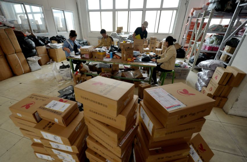 TO GO WITH China-economy-retail-Alibaba-family,FOCUS by Tom HANCOCK This image taken on April 24, 2014 shows workers at a handbag factory packaging up orders to be sold through the Chinese Internet e-commerce site Taobao in Baigou, Hebei Province. The Alibaba Group, which dominates China's e-commerce market, combines aspects of eBay, Amazon, PayPal and other Western tech darlings, and according to analysts an investor frenzy could drive its value as high as 200 billion USD when it goes public in the US later this year. One of Alibaba's main assets, the sprawling e-commerce site Taobao -- or 'search for treasure' -- enables him to offer his locally made bags to millions of potential Chinese customers. AFP PHOTO / Mark RALSTON (Photo credit should read MARK RALSTON/AFP/Getty Images)
