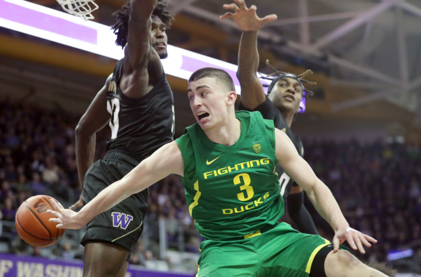 SEATTLE, WASHINGTON - JANUARY 18: Payton Pritchard #3 of the Oregon Ducks passes the ball against Isaiah Stewart #33 (L) and Jaden McDaniels #0 of the Washington Huskies in the second half during their game at Hec Edmundson Pavilion on January 18, 2020 in Seattle, Washington. (Photo by Abbie Parr/Getty Images)
