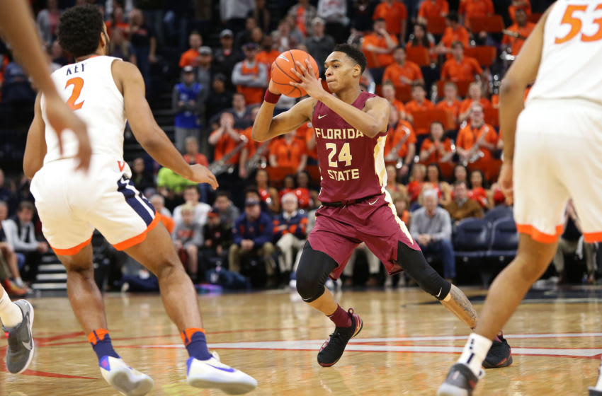 CHARLOTTESVILLE, VA - JANUARY 28: Devin Vassell #24 of the the Florida State Seminoles passes around Braxton Key #2 of the the Virginia Cavaliers in the first half during a game at John Paul Jones Arena on January 28, 2020 in Charlottesville, Virginia. (Photo by Ryan M. Kelly/Getty Images)