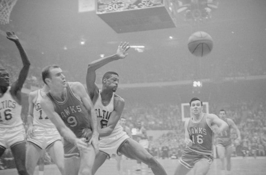 (Original Caption) Free Ball. Boston: St. Louis Hawks' Cliff Hagan starts for the ball as it bounces off the fingertips of Bill Russell (6) of the Celtics, during the second period of their NBA Championship game in the Boston Garden April 11th. The Celts took their third consecutive NBA title by downing St. Louis, 121-112 in the fifth game of a seven game series. Bob Petit (9) of the Hawks is also in the play.