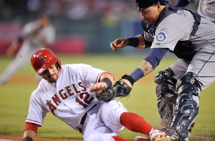 September 26, 2015; Anaheim, CA, USA; Los Angeles Angels second baseman Johnny Giavotella (12) is out at home against the tag of Seattle Mariners catcher Jesus Sucre (2) in the second inning at Angel Stadium of Anaheim. Mandatory Credit: Gary A. Vasquez-USA TODAY Sports