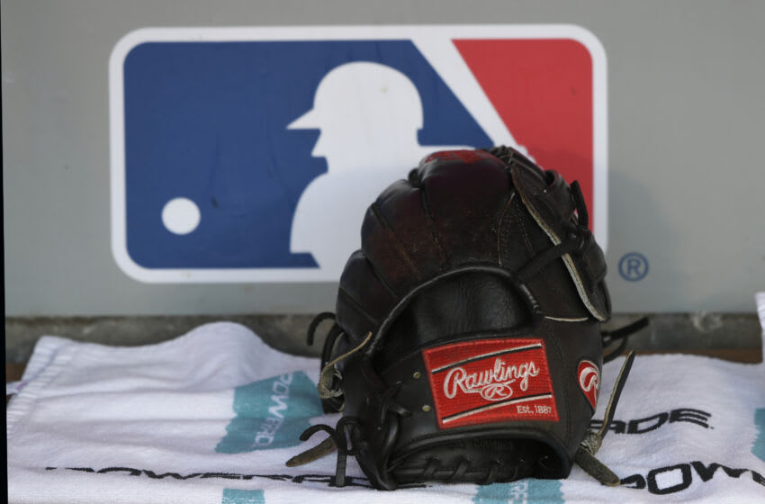 ANAHEIM, CA - SEPTEMBER 15: A Rawlings baseball glove sits in the Seattle Mariners dugout in front of an MLB logo before a game with the Los Angeles Angels of Anaheim at Angel Stadium on September 15, 2018 in Anaheim, California. (Photo by John McCoy/Getty Images)