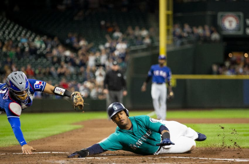 SEATTLE, WA - SEPTEMBER 28: Jean Segura #2 of the Seattle Mariners beats the tag by Robinson Chirinos #61 of the Texas Rangers in the second inning to score on a single by Nelson Cruz #32 at Safeco Field on September 28, 2018 in Seattle, Washington. (Photo by Lindsey Wasson/Getty Images)