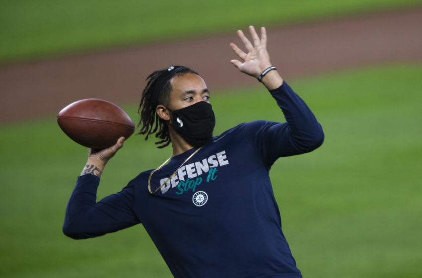SEATTLE, WA - AUGUST 06: J.P. Crawford #3 of the Seattle Mariners throws a football with teammates before the game against the Los Angeles Angels at T-Mobile Park on August 6, 2020 in Seattle, Washington. The Angels beat the Mariners 6-1. (Photo by Lindsey Wasson/Getty Images)