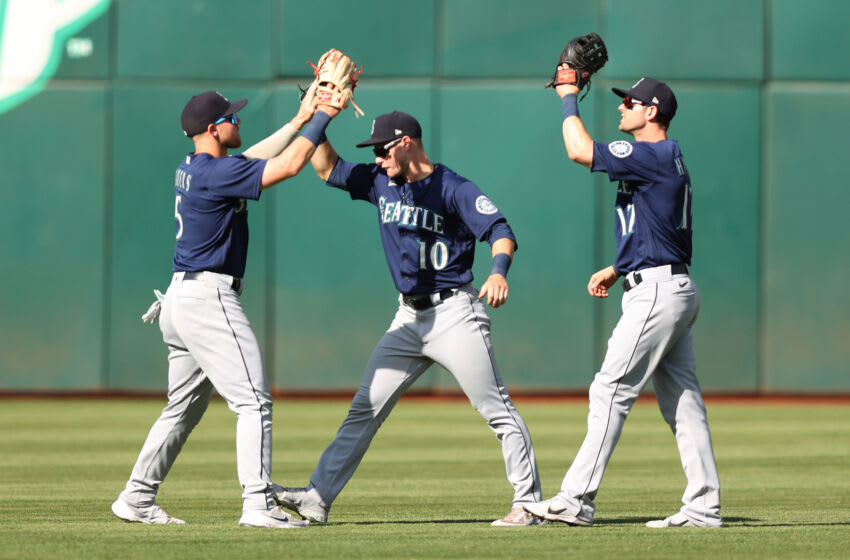 OAKLAND, CALIFORNIA - SEPTEMBER 23: Jake Bauers #5, Jarred Kelenic #10, and Mitch Haniger #17 of the Seattle Mariners celebrate after they beat the Oakland Athletics at RingCentral Coliseum on September 23, 2021 in Oakland, California. (Photo by Ezra Shaw/Getty Images)