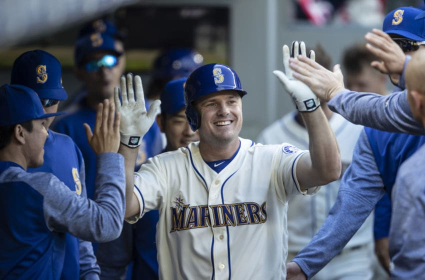SEATTLE, WA - MARCH 31: Jay Bruce #32 of the Seattle Mariners is congraulted by teammates in the dugout after hitting a solo home run off of relief pitcher Brian Johnson #61 of the Boston Red Sox during the fourth inning of a game at T-Mobile Park on March 31, 2019 in Seattle, Washington. (Photo by Stephen Brashear/Getty Images)