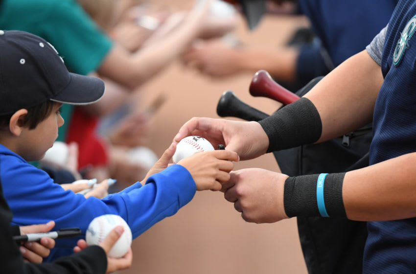 PEORIA, ARIZONA - MARCH 21: A young fan gets an autograph prior to a spring training game between the Cincinnati Reds and the Seattle Mariners at Peoria Stadium on March 21, 2019 in Peoria, Arizona. (Photo by Norm Hall/Getty Images)