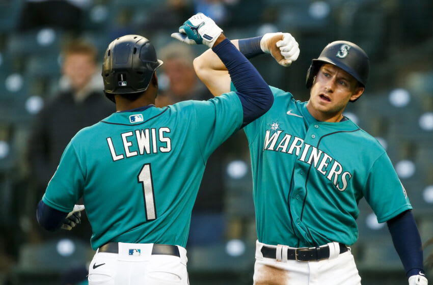 May 28, 2021; Seattle, Washington, USA; Seattle Mariners left fielder Kyle Lewis (1) bumps forearms with left fielder Jarred Kelenic (10) after hitting a two-run home run against the Texas Rangers during the third inning at T-Mobile Park. Kelenic also scored a run on the hit. Mandatory Credit: Joe Nicholson-USA TODAY Sports