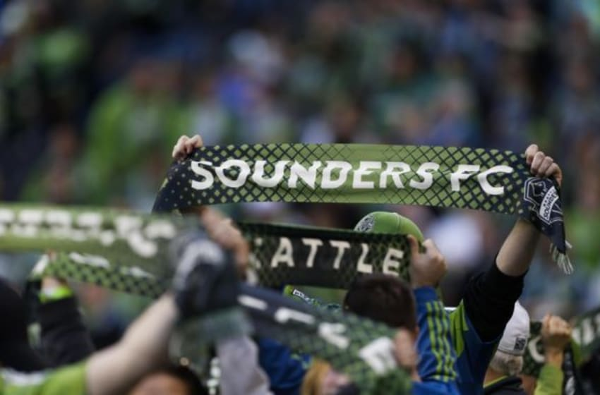Mar 8, 2015; Seattle, WA, USA; Seattle Sounders FC fans lift their scarves before a game against the New England Revolution at CenturyLink Field. Seattle defeated New England 3-0. Mandatory Credit: Jennifer Buchanan-USA TODAY Sports