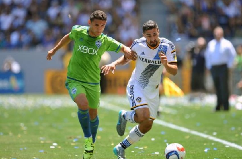 August 9, 2015; Carson, CA, USA; Los Angeles Galaxy midfielder Sebastian Lletget (17) moves the ball against Seattle Sounders midfielder Cristian Roldan (7) during the first half at StubHub Center. Mandatory Credit: Gary A. Vasquez-USA TODAY Sports