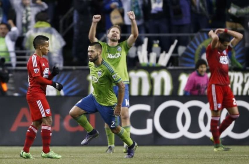 Nov 1, 2015; Seattle, WA, USA; Seattle Sounders FC defender Chad Marshall (14) raises his arms in the air as FC Dallas defender Matt Hedges (24) holds his head after forward Clint Dempsey (2) scored the goal ahead goal during the second half at CenturyLink Field. Seattle won 2-1. Mandatory Credit: Jennifer Buchanan-USA TODAY Sports