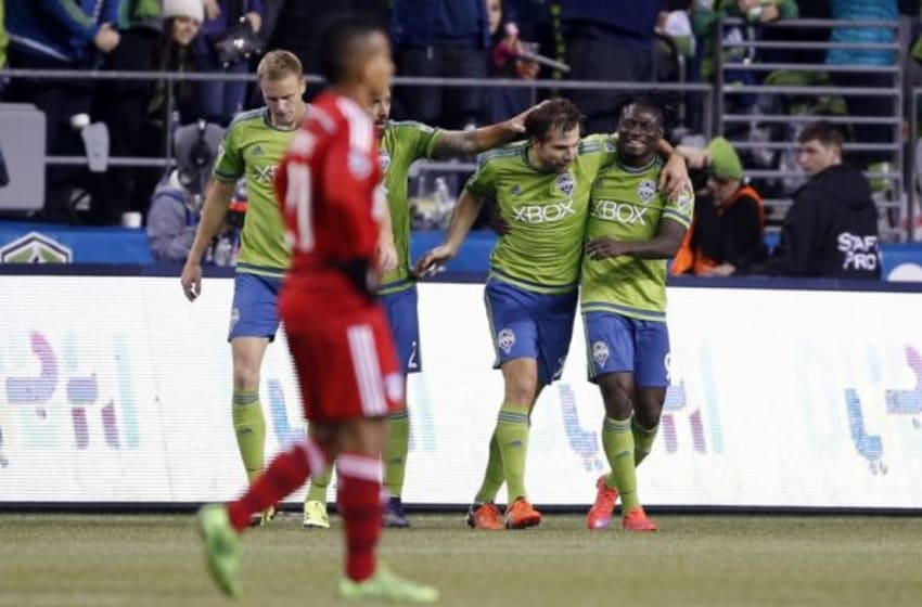 Nov 1, 2015; Seattle, WA, USA; Seattle Sounders FC midfielder Andreas Ivanschitz (23) is congratulated by forward Clint Dempsey (2) and forward Obafemi Martins (9) as FC Dallas midfielder Michael Barrios (21) walks back down the field during the second half at CenturyLink Field. Mandatory Credit: Jennifer Buchanan-USA TODAY Sports