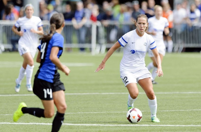 Aug 31, 2014; Tukwila, WA, USA; FC Kansas City forward Lauren Holiday (12) dribbles the ball while being defended by Seattle Reign FC defender Stephanie Cox (14) during the game at Starfire Soccer Stadium. Kansas City defeated Seattle 2-1. Mandatory Credit: Steven Bisig-USA TODAY Sports