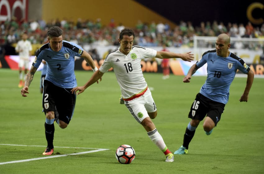 GLENDALE, ARIZONA - JUNE 05: Andres Guardado of Mexico brings the ball up field between Jose Maria Gimenez and Maximiliano Pereira of Uruguay during the second half of a group C match at University of Phoenix Stadium as part of Copa America Centenario US 2016 on June 05, 2016 in Glendale, Arizona, US. Mexico won 3-1. (Photo by Norman Hall/LatinContent/Getty Images)
