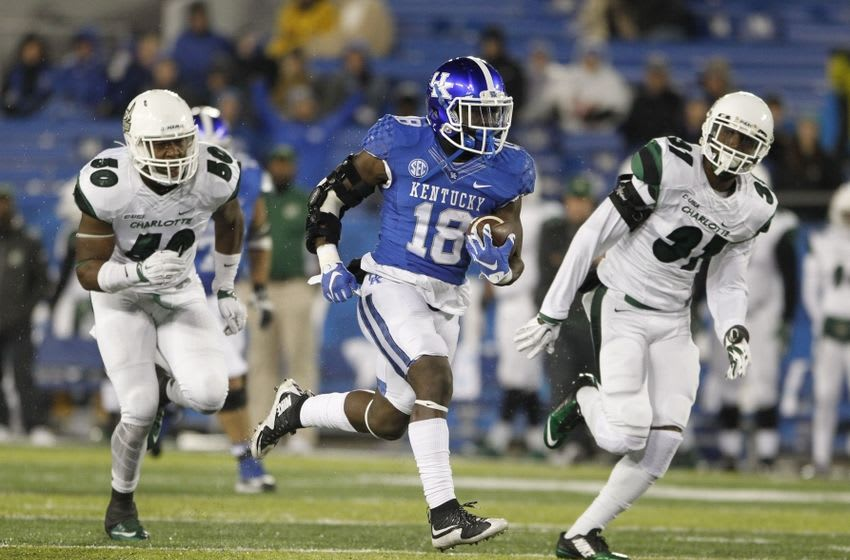 Nov 21, 2015; Lexington, KY, USA; Kentucky Wildcats running back Stanley Boom Williams (18) runs the ball against Charlotte 49ers offensive lineman Jarred Barr (50) and defensive back Markevis Davis (31) in the second hafl at Commonwealth Stadium. Mandatory Credit: Mark Zerof-USA TODAY Sports