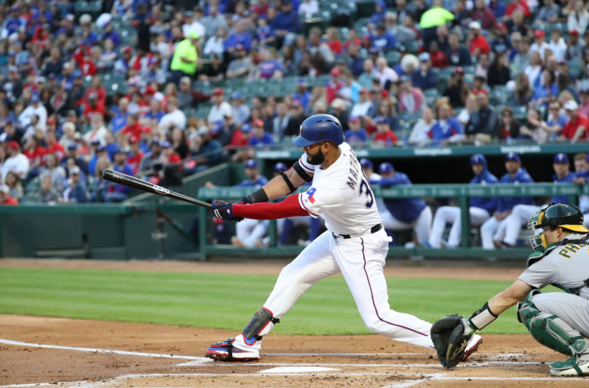 ARLINGTON, TEXAS - APRIL 12: Nomar Mazara #30 of the Texas Rangers hits a rbi single against the Oakland Athletics in the first inning at Globe Life Park in Arlington on April 12, 2019 in Arlington, Texas. (Photo by Ronald Martinez/Getty Images)
