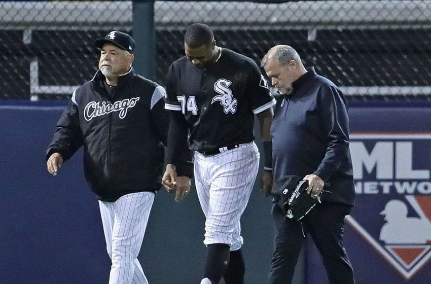 CHICAGO, ILLINOIS - APRIL 26: Manager Rick Renteria of the Chicago White Sox (L) escorts Eloy Jimenez #74 off the field after Jimenez hit the wall trying to catch a home run ball against the Detroit Tigers at Guaranteed Rate Field on April 26, 2019 in Chicago, Illinois. (Photo by Jonathan Daniel/Getty Images)