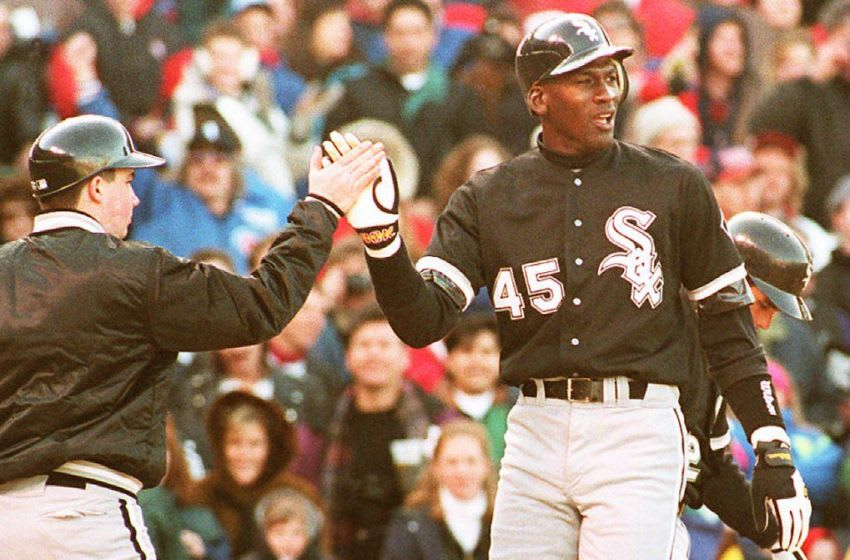 Chicago White Sox outfielder Michael Jordan (R) is greeted by a unidentified batboy at Chicago's Wrigley Field, 07 April 1994, after scoring on a sixth inning home run during a crosstown exhibition game against the Cubs. Jordan, who will return to the minor leagues after the game, had two hits as the teams tied 4-4. (Photo by EUGENE GARCIA / AFP) (Photo credit should read EUGENE GARCIA/AFP via Getty Images)