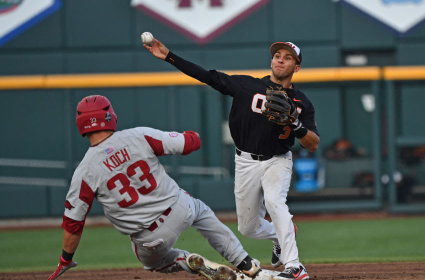 Omaha, NE - JUNE 26: Infielder Nick Madrigal #3 of the Oregon State Beavers turns a double play with a throw to first over catcher Grant Koch #33 of the Arkansas Razorbacks in the third inning during game one of the College World Series Championship Series on June 26, 2018 at TD Ameritrade Park in Omaha, Nebraska. (Photo by Peter Aiken/Getty Images)