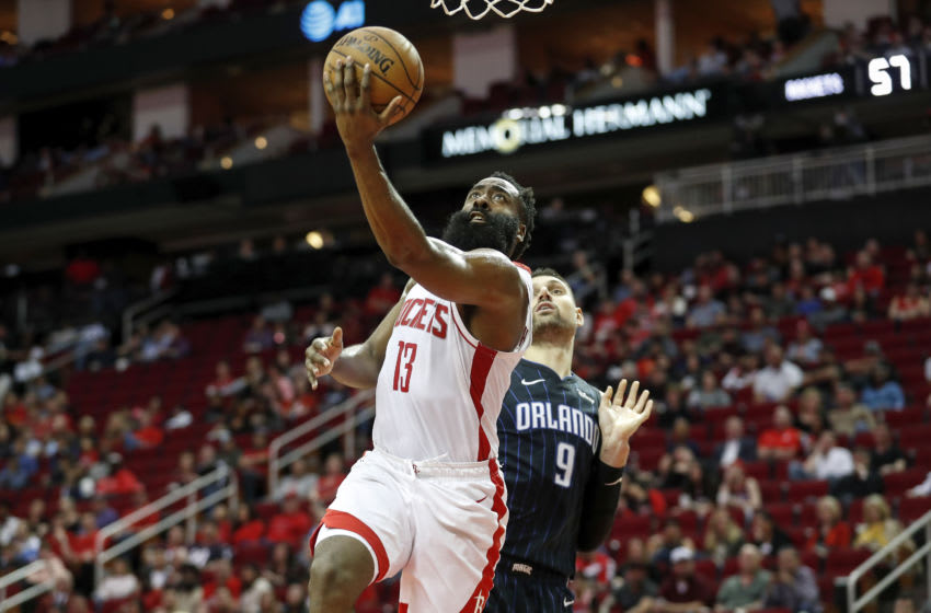 James Harden #13 of the Houston Rockets drives to the basket while defended by Nikola Vucevic #9 of the Orlando Magic (Photo by Tim Warner/Getty Images)