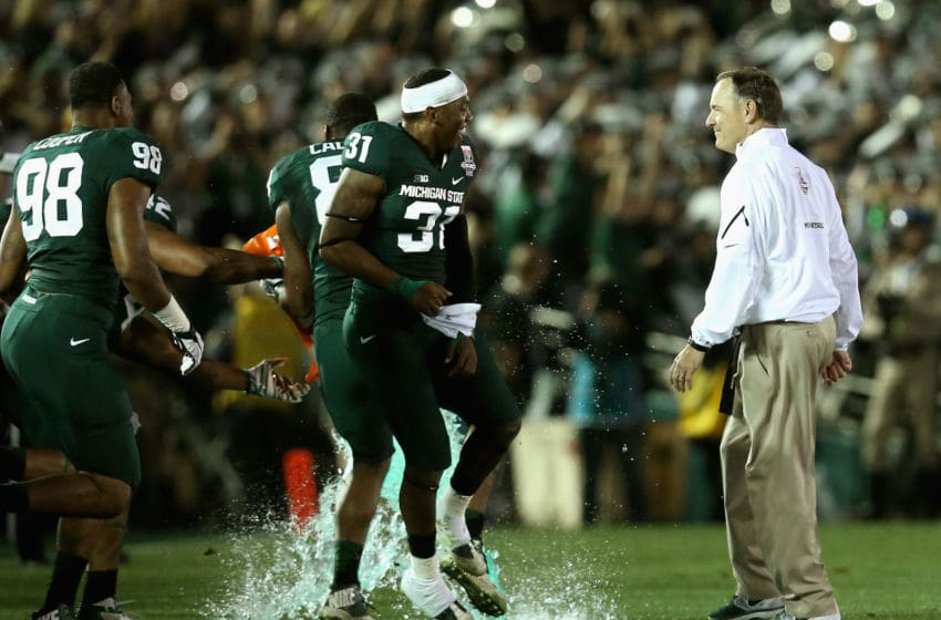 PASADENA, CA - JANUARY 01: Michigan State Spartans head coach Mark Dantonio is missed as defensive end Shilique Calhoun #89 and cornerback Darqueze Dennard #31 pour the Gatorade on the field after defeating the Stanford Cardinal 24-20 during the 100th Rose Bowl Game presented by Vizio at the Rose Bowl on January 1, 2014 in Pasadena, California. (Photo by Stephen Dunn/Getty Images)