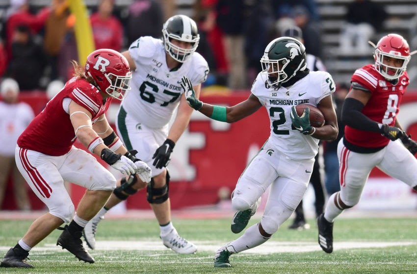 PISCATAWAY, NEW JERSEY - NOVEMBER 23: Elijah Collins #24 of the Michigan State Spartans stiff arms Mike Tverdov #97 of the Rutgers Scarlet Knights during the second half of their game at SHI Stadium on November 23, 2019 in Piscataway, New Jersey. (Photo by Emilee Chinn/Getty Images)