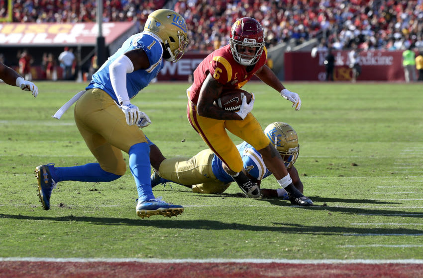 LOS ANGELES, CALIFORNIA - NOVEMBER 23: Darnay Holmes #1 and Stephan Blaylock #4 of the UCLA Bruins tackle Michael Pittman Jr. #6 of the USC Trojans during the first half of a game at Los Angeles Memorial Coliseum on November 23, 2019 in Los Angeles, California. (Photo by Sean M. Haffey/Getty Images)