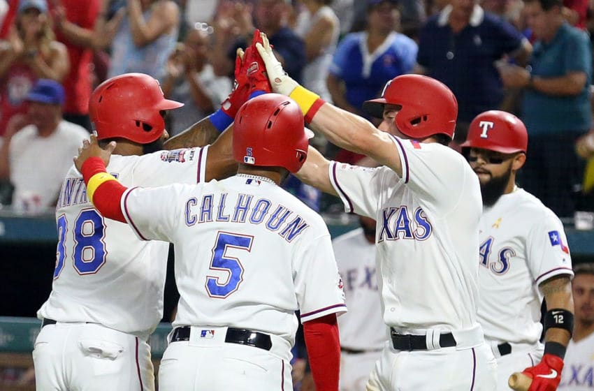 ARLINGTON, TEXAS - SEPTEMBER 13: Danny Santana #38 of the Texas Rangers is greeted by Willie Calhoun #5 and Nick Solak #15 after a three-run home run in the third inning against the Oakland Athletics at Globe Life Park in Arlington on September 13, 2019 in Arlington, Texas. (Photo by Richard Rodriguez/Getty Images)